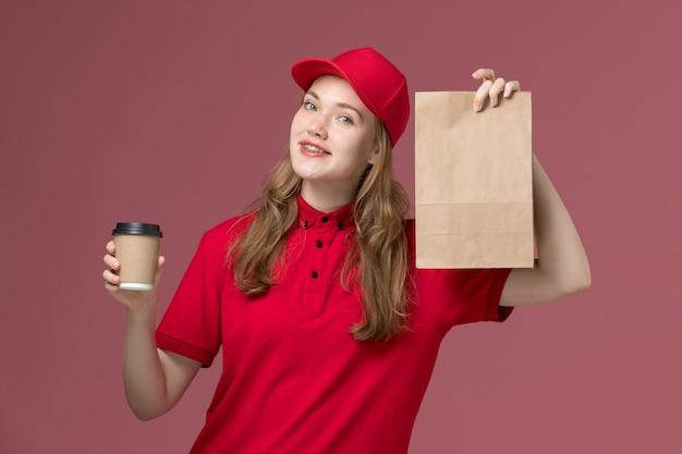 Kurierka w czerwonym mundurze trzyma filiżankę kawy i pakiet żywności na różowym, jednolitym zleceniu dostawy usług