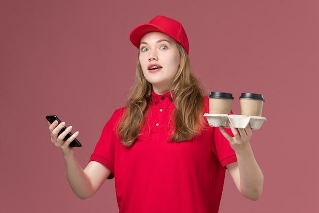 Kurierka w czerwonym mundurze trzyma filiżanki do kawy i smartfon na różowym, jednolitym zleceniu dostawy usług