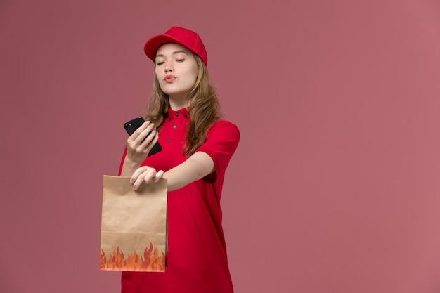 Kurierka w czerwonym mundurze trzyma paczkę z jedzeniem i używa swojego telefonu na jasnoróżowej, mundurowej dostawie pracownika serwisu