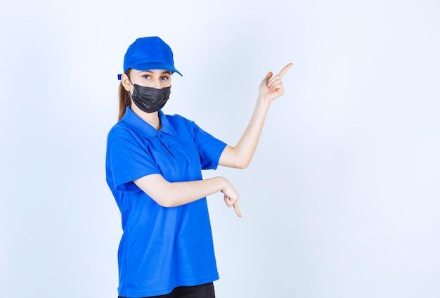Kurierka w masce i niebieskim mundurze i pokazująca coś po prawej stronie