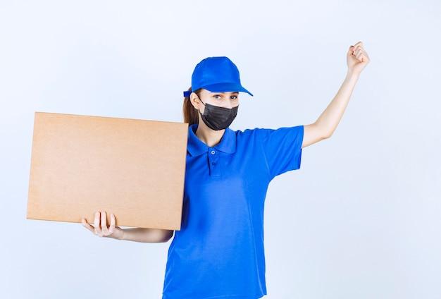 Kurierka w masce i niebieskim mundurze trzymająca dużą kartonową paczkę i pokazująca pięść