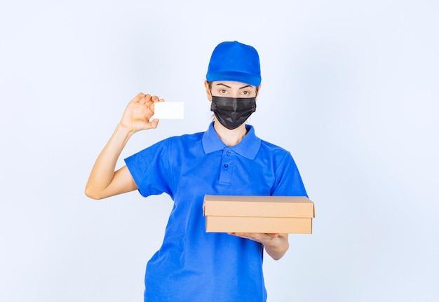 Kurierka w niebieskim mundurze i masce na twarz dostarczająca kartonową paczkę i prezentująca swoją wizytówkę.