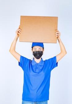 Kurierka w niebieskim mundurze i masce na twarz dostarczająca klientowi karton.