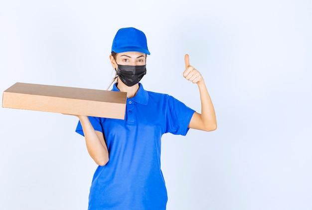 Kurierka w niebieskim mundurze i masce na twarz, trzymająca karton i pokazująca znak przyjemności.
