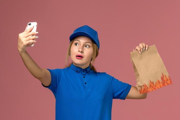 Kurierka w niebieskim mundurze robi selfie z pakietem żywności na jasnoróżowym, mundurowym zleceniu dostawy