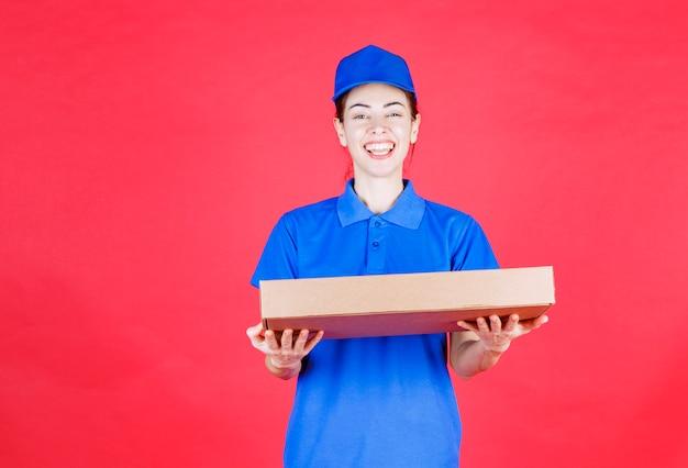 Kurierka w niebieskim mundurze trzyma kartonowe pudełko pizzy na wynos.