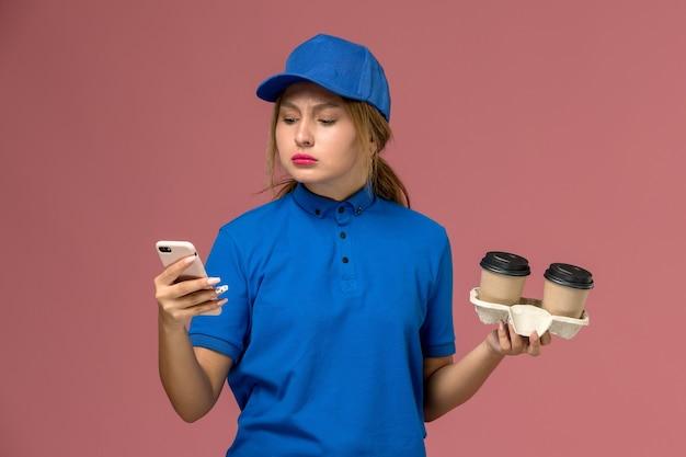 Kurierka w niebieskim mundurze, trzymając filiżanki kawy i używając swojego telefonu na różowym, mundurze pracownika serwisu