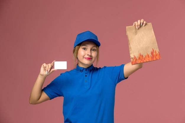 Kurierka w niebieskim mundurze trzymająca białą plastikową kartę i opakowanie żywności na jasnoróżowym, jednolita usługa dostawy