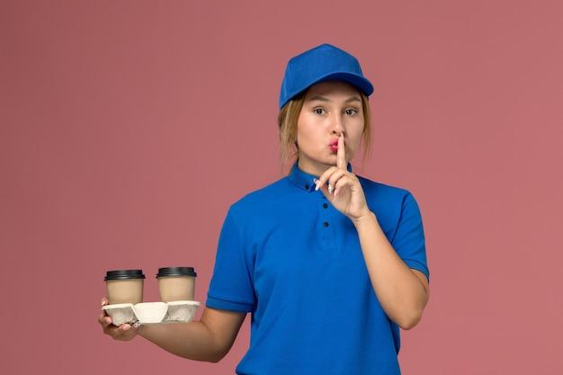 Kurierka w niebieskim mundurze trzymająca filiżanki kawy pokazująca znak ciszy na różowym, jednolita dostawa