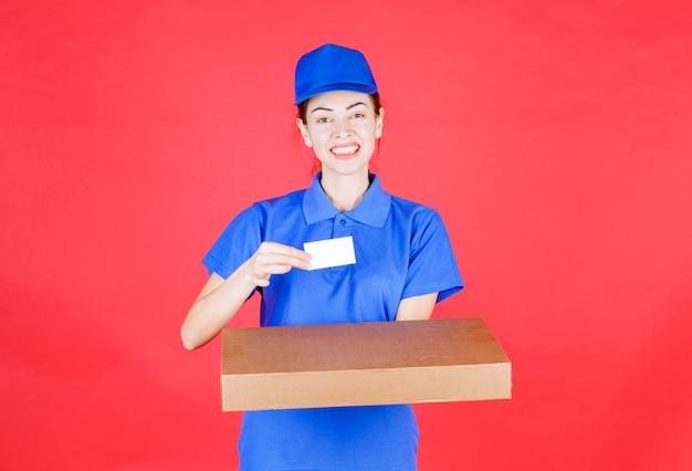 Kurierka w niebieskim mundurze trzymająca karton i prezentująca swoją wizytówkę.