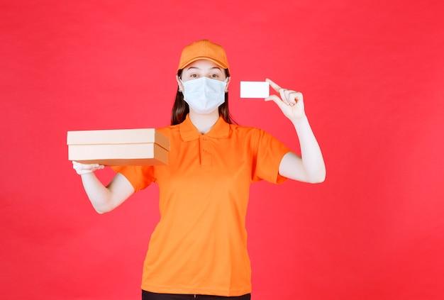 Kurierka w pomarańczowym dresscode i masce trzymająca kartonowe pudełko i prezentująca swoją wizytówkę