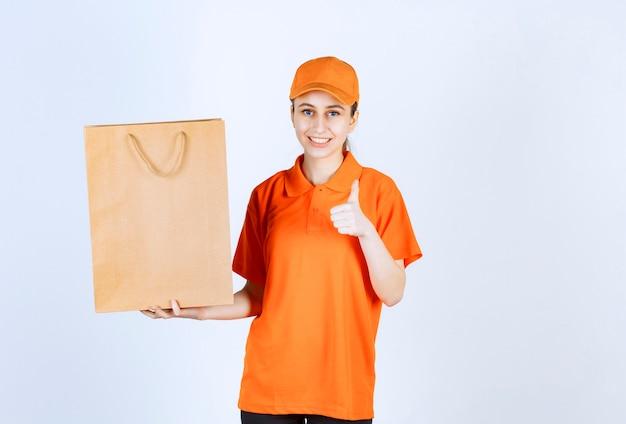 Kurierka w pomarańczowym mundurze dostarczająca torbę na zakupy i pokazująca pozytywny znak ręki