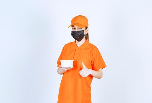 Kurierka w pomarańczowym mundurze i czarnej masce, trzymająca plastikowy kubek i pokazująca pozytywny znak ręki