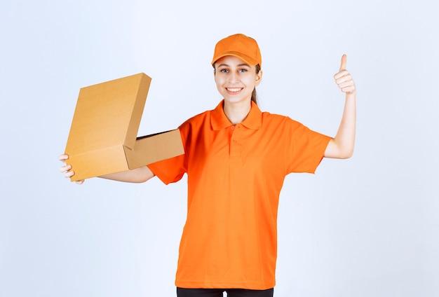 Kurierka w pomarańczowym mundurze trzymająca otwarte kartonowe pudełko i pokazująca pozytywny znak ręki.