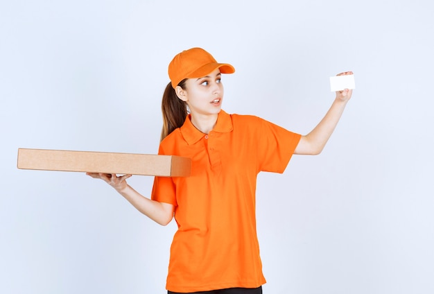 Kurierka w pomarańczowym mundurze trzymająca pudełko po pizzy na wynos i prezentująca swoją wizytówkę