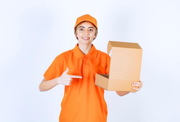 Kurierka w pomarańczowym mundurze z otwartym kartonowym pudełkiem