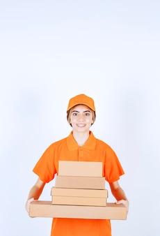 Kurierka w pomarańczowym mundurze z zapasem kartonowych paczek