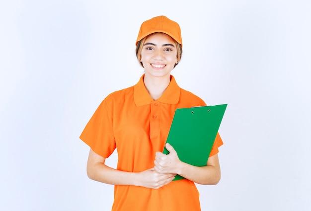 Kurierka w pomarańczowym mundurze z zieloną listą klientów