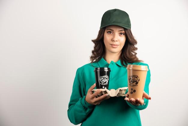 Kurierka w zielonym mundurze trzymając filiżanki kawy.