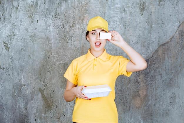 Kurierka w żółtym mundurze dostarczająca białe pudełko na wynos i prezentująca swoją wizytówkę.