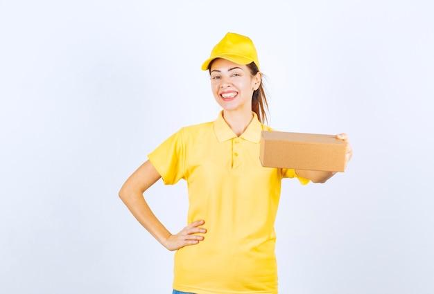 Kurierka w żółtym mundurze dostarczająca kartonową paczkę i pozytywnie nastrajająca.
