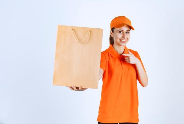 Kurierka w żółtym mundurze dostarczająca torbę na zakupy i wprowadzająca ją