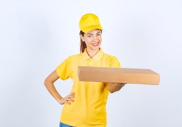 Kurierka w żółtym mundurze dostarczyła tekturową paczkę pod właściwy adres.