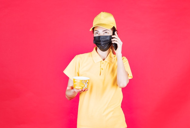 Kurierka w żółtym mundurze i czarnej masce dostarcza kubek z makaronem podczas rozmowy z telefonem