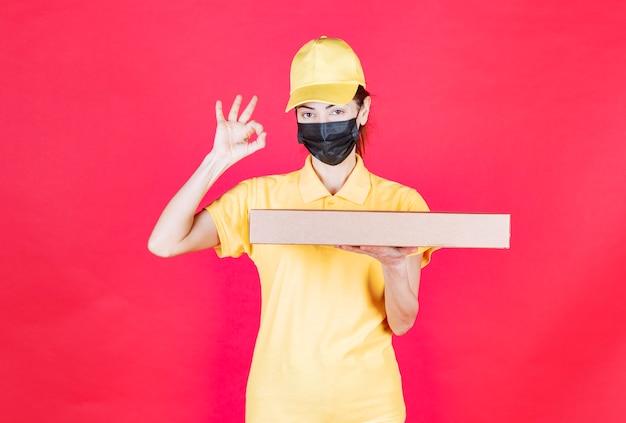 Kurierka w żółtym mundurze i czarnej masce trzymająca karton i pokazująca pozytywny znak ręki