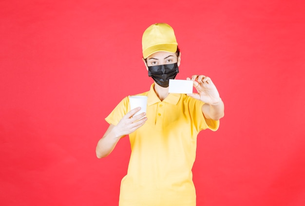 Kurierka w żółtym mundurze i czarnej masce trzymająca kubek na wynos i prezentująca swoją wizytówkę