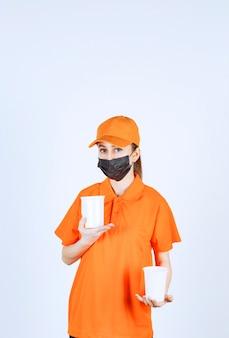 Kurierka w żółtym mundurze i czarnej masce trzymająca napoje na wynos w plastikowych kubkach w obu rękach