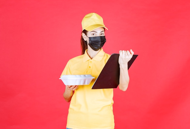 Kurierka w żółtym mundurze i czarnej masce trzymająca paczkę na wynos i czytająca listę klientów