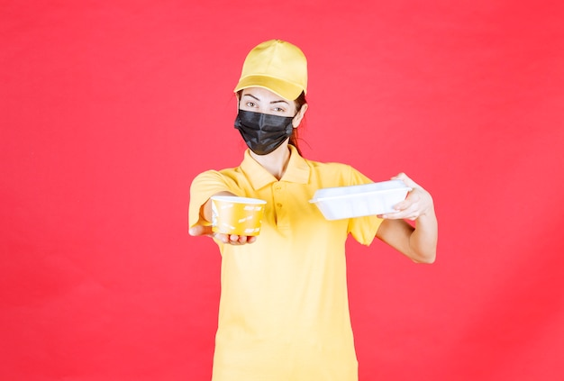 Kurierka w żółtym mundurze i czarnej masce, trzymająca paczkę na wynos i kubek z makaronem
