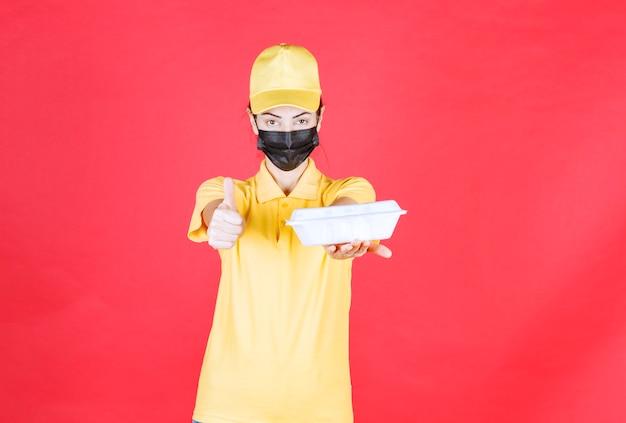 Kurierka w żółtym mundurze i czarnej masce trzymająca paczkę na wynos i pokazująca pozytywny znak ręki