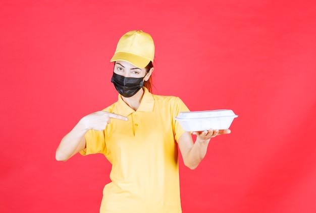 Kurierka w żółtym mundurze i czarnej masce trzymająca paczkę na wynos