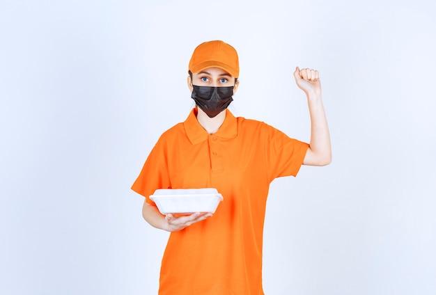 Kurierka w żółtym mundurze i czarnej masce, trzymająca plastikowe pudełko z jedzeniem na wynos i pokazująca pięść.