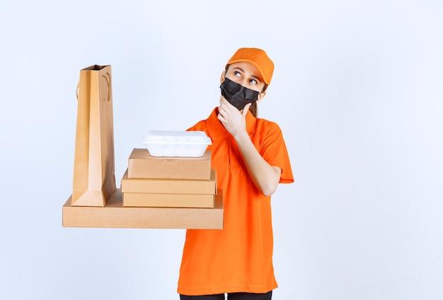 Kurierka w żółtym mundurze i czarnej masce trzymająca wiele kartonowych paczek, pudełko na wynos i torbę na zakupy, wyglądając na zdezorientowaną i zamyśloną