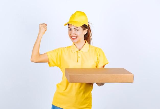 Kurierka w żółtym mundurze trzymająca kartonową paczkę i pokazująca pięść.