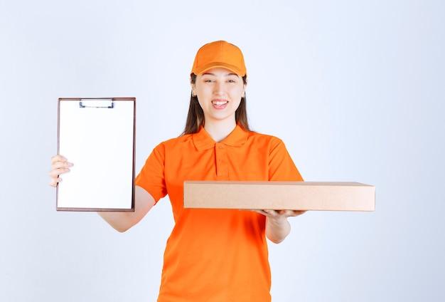 Kurierka w żółtym mundurze trzymająca kartonowe pudełko na wynos i przedstawiająca listę podpisów.