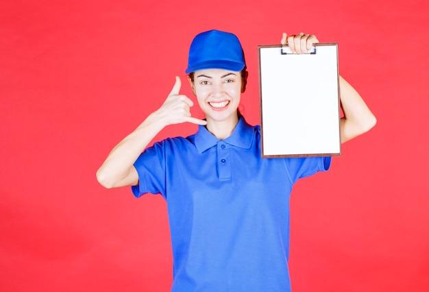 Kurierska dziewczyna w niebieskim mundurze trzymająca listę zadań i prosząca o telefon.