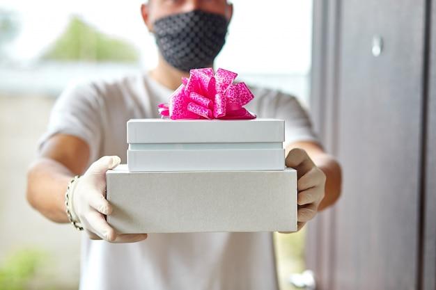 Kurierskie prezenty zbliżeniowe, pudełko upominkowe podczas epidemii koronawirusa.