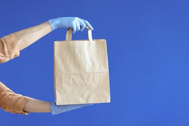 Kurierskie ręce w gumowych rękawiczkach trzymające papierową torbę na niebieskim tle