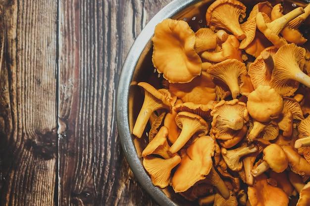 Kurki leśne na drewnianym stole. świeże grzyby do gotowania.