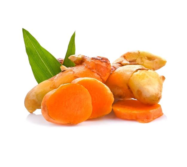 Kurkuma (curcuma longa linn); korzeń pokrojony w zielone liście na białym tle. zioło o wysokiej zawartości witaminy c i dla ochrony przed wirusami.