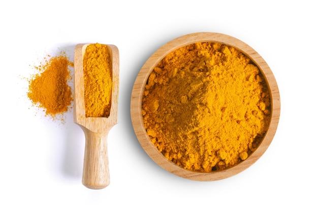 Kurkuma (kurkuma) stos proszku w drewnianej misce i czerpak na białym tle