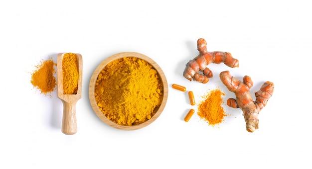 Kurkuma (kurkuma) w proszku stos w misce z drewna i kapsułki na białym tle
