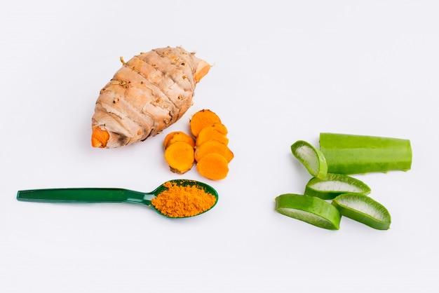 Kurkuma w proszku i plasterek kurkumy z plasterkiem aloesu na białym tle składnik ziołowy, widok z góry.