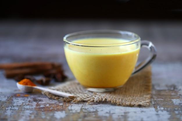 Kurkuma z przyprawami w kubku. złote mleko kurkumowe. indyjski napój zdrowotny. selektywne ustawianie ostrości.