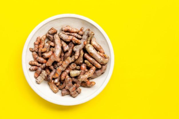 Kurkumowy korzeń na garncarstwo talerzu na żółtym tle.