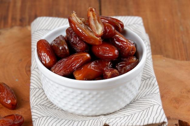 Kurma lub słodkie suszone owoce palmowe w misce na białym tle